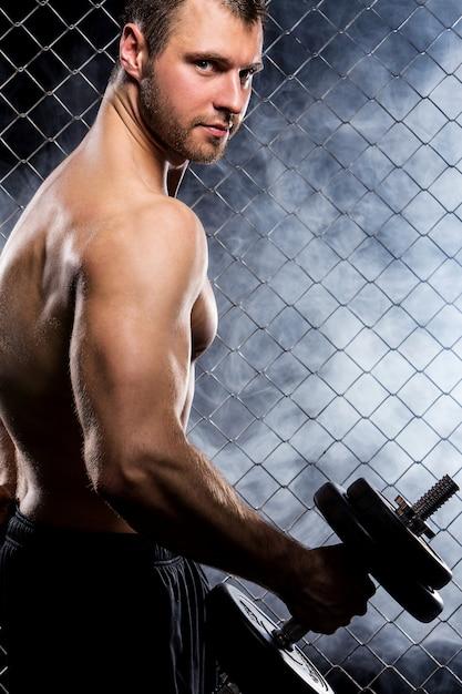 Ragazzo potente con manubri che mostrano i muscoli sul recinto Foto Gratuite