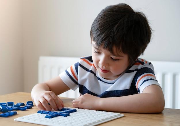 Ragazzo prescolare che gioca il gioco inglese di upwords, bambino che gioca il gioco della lettera a casa. Foto Premium