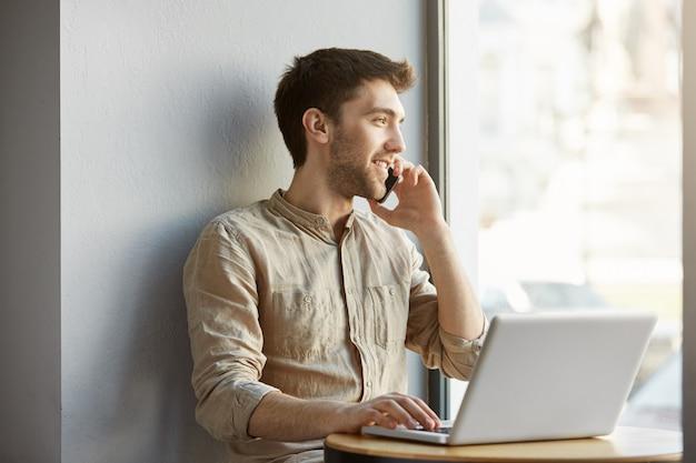 Ragazzo rasato attraente allegro che si siede nello spazio di coworking, che lavora al computer portatile e che parla sul telefono con l'amica circa la data nella sera. Foto Gratuite