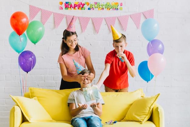 Ragazzo seduto sul divano che riceve il regalo di compleanno a sorpresa dai suoi amici Foto Gratuite