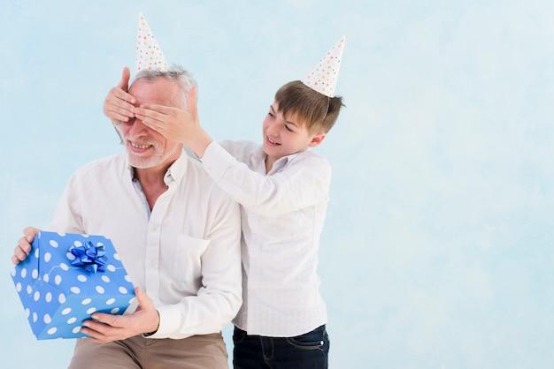 Ragazzo sorridente adorabile che dà regalo sorpreso a suo nonno coprendo i suoi occhi contro fondo blu Foto Gratuite