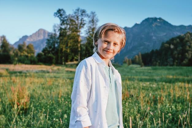 Ragazzo sorridente biondo che esamina macchina fotografica su fondo della vista meravigliosa del prato e delle montagne verdi, stile di vita di avventura di viaggio della famiglia Foto Premium