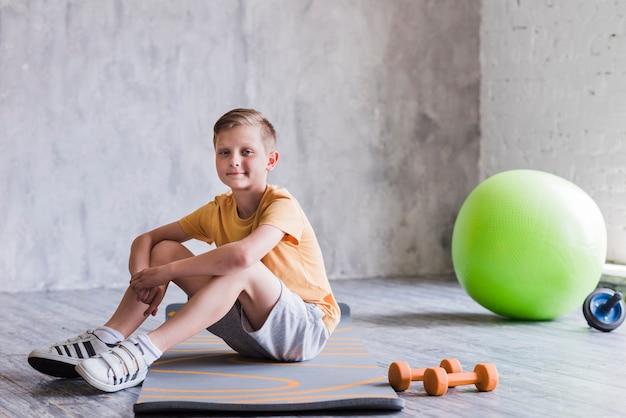 Ragazzo sorridente che si siede sulla stuoia di esercitazione con il dumbbell; palla pilates e scivolo a rullo Foto Gratuite