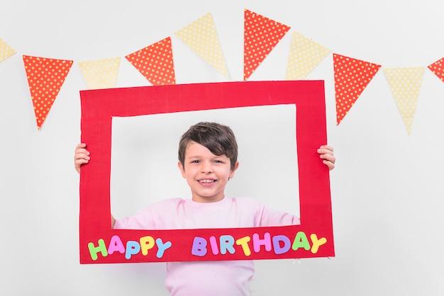 Ragazzo sorridente che tiene la struttura rossa di compleanno nel partito Foto Gratuite