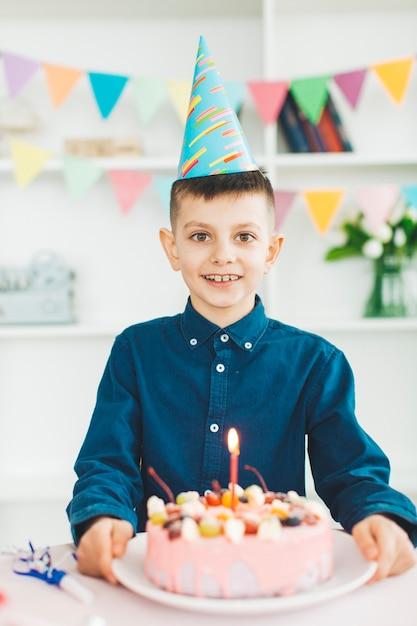 Ragazzo sorridente con una torta di compleanno Foto Gratuite