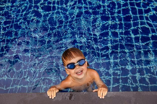 Ragazzo sorridente in occhiali in acqua vicino al bordo della piscina Foto Premium