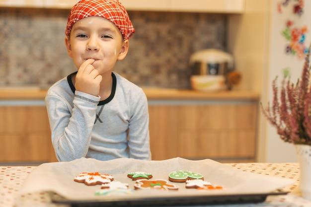 Ragazzo sveglio che gode del gusto dei biscotti di natale di appoggio freschi. Foto Premium