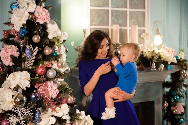 Ragazzo sveglio e sua madre che decorano l'albero di natale per le vacanze Foto Premium