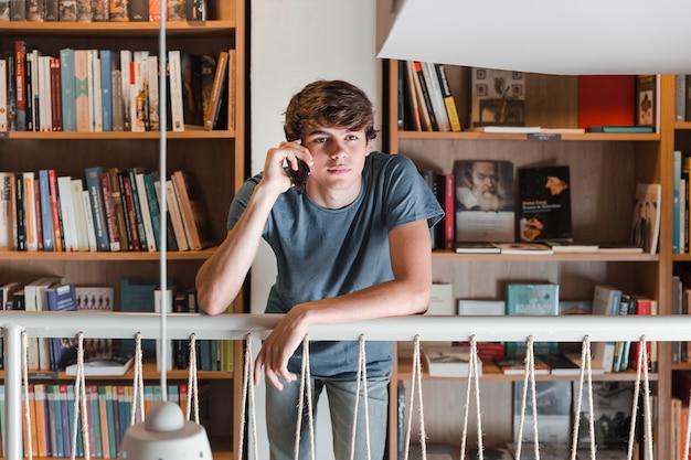 Ragazzo teenager che parla sullo smartphone in biblioteca Foto Gratuite