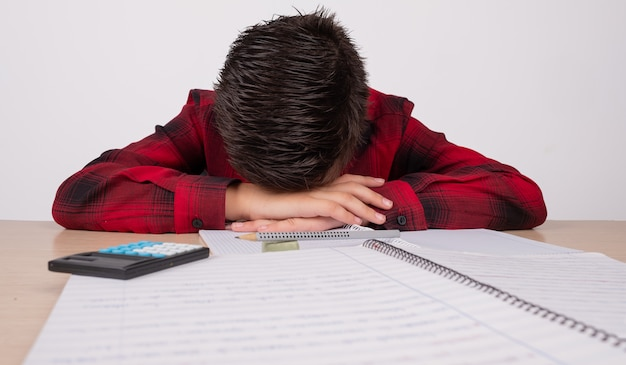 Ragazzo triste con le mani sulla sua testa al tavolo a scuola Foto Premium