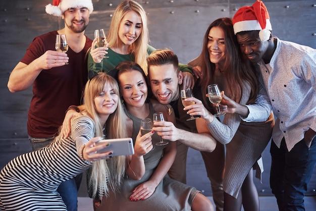 Raggruppa i bei giovani che fanno selfie nella festa di capodanno, le ragazze e i ragazzi dei migliori amici che si divertono insieme, posando le persone di stile di vita emotivo. cappelli di babbo natale e bicchieri di champagne nelle loro mani Foto Premium