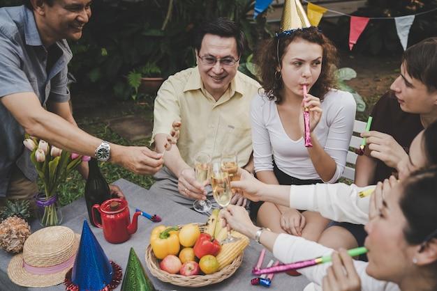 Raggruppi gli amici di anziano e di giovane felice e divertimento nel partito con il giardino del champagne a casa Foto Premium