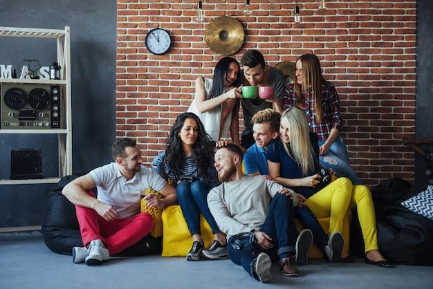 Raggruppi il ritratto dei ragazzi e delle ragazze multietnici con i vestiti alla moda variopinti che tengono l'amico che posa su un muro di mattoni, gente urbana di stile che si diverte, s circa lo stile di vita di insieme della gioventù Foto Premium