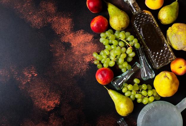 Rakia o rakija il tradizionale brandy alla frutta balcanica. i frutti di cui producono rakia. frutta, bottiglie e bicchieri per l'alcol. vista dall'alto. sfondo scuro vintage. spazio per il testo Foto Premium