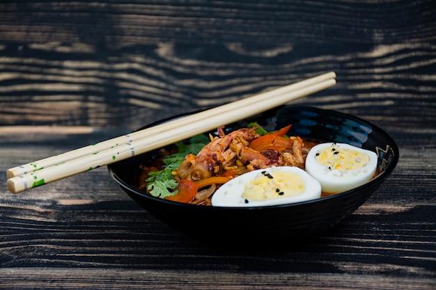 Ramen giapponese con frutti di mare, erbe e uova in salamoia Foto Premium