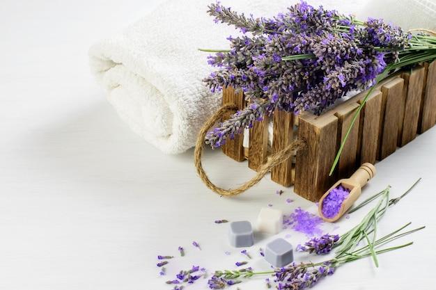 Rametti di lavanda, sale aromatico e sapone, asciugamani bianchi sul tavolo di legno. stile di vita rustico benessere benessere, assistenza sanitaria. Foto Premium