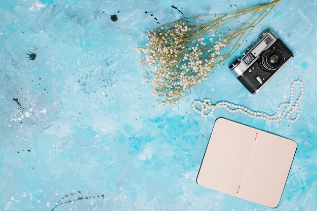 Rami di fiori con fotocamera, notebook e perline sul tavolo blu Foto Gratuite
