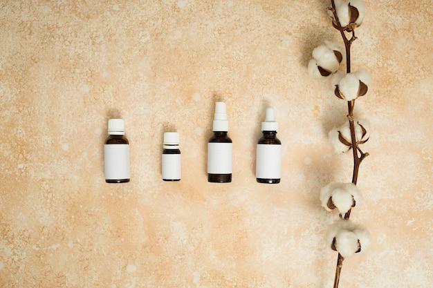 Ramo di cotone con diversi tipi di bottiglie di olio essenziale su sfondo beige con texture Foto Gratuite