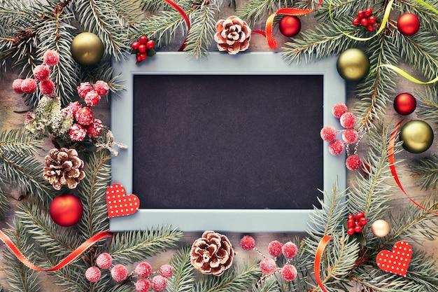 Ramoscello di abete decorato con palline, bacche e stelle con lavagna Foto Premium