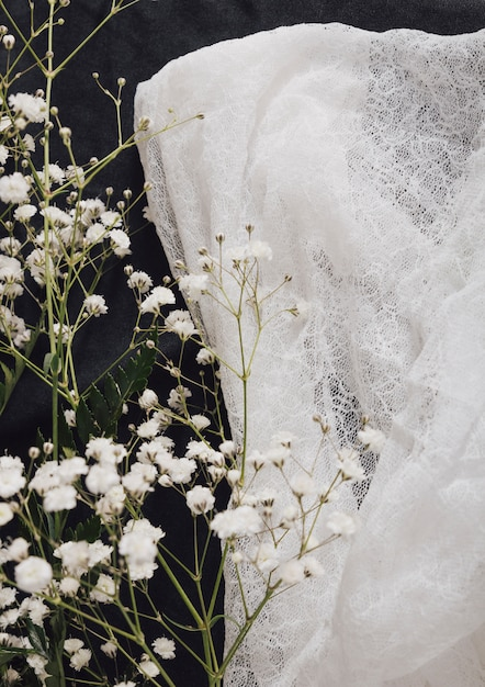 Ramoscello di fiore fresco vicino tessile bianco Foto Gratuite