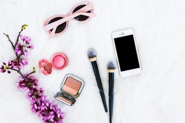 Ramoscello di fiori viola con cipria compatta; pennelli per il trucco; telefono cellulare e occhiali da sole sullo sfondo di pelliccia Foto Gratuite
