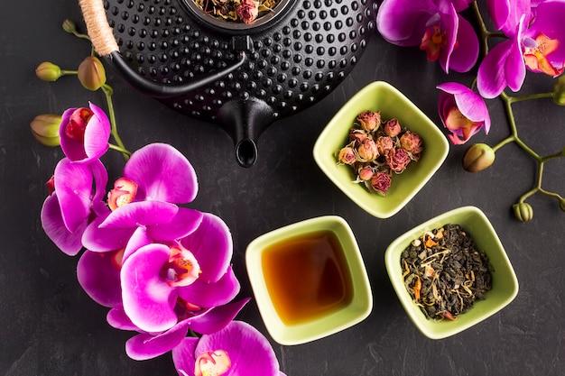 Ramoscello e tisana rosa freschi del fiore dell'orchidea su fondo nero Foto Gratuite