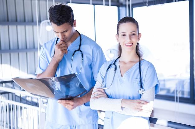Rapporto d'esame sorridente del raggio di ascia di medico con il suo collega in ospedale Foto Premium