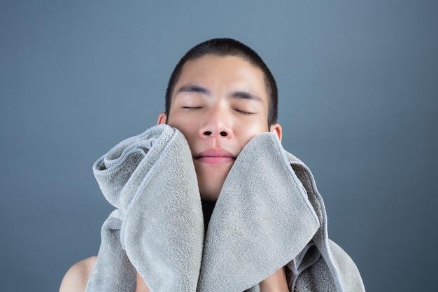 Rasatura dei giovani bei con un asciugamano su gray Foto Gratuite