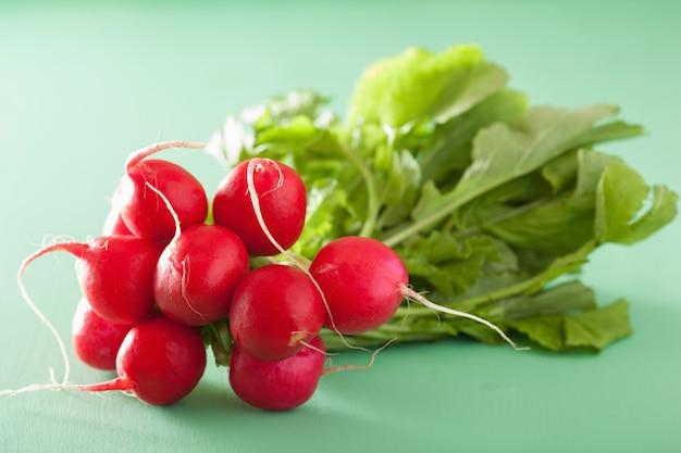 Ravanello fresco con foglie sul tavolo verde Foto Premium