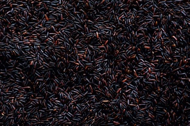 Raw rosso scuro, riso viola balck, trama. modello riceberry. ingrediente alimentare vista dall'alto, concetto di stile di vita sano. Foto Premium