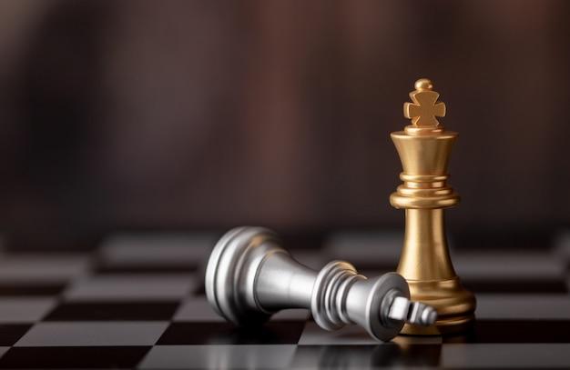 Re d'oro in piedi e argento che cade sulla scacchiera Foto Premium