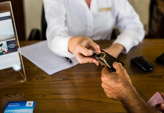 Receptionist che fornisce la chiave della stanza ad un cliente Foto Premium