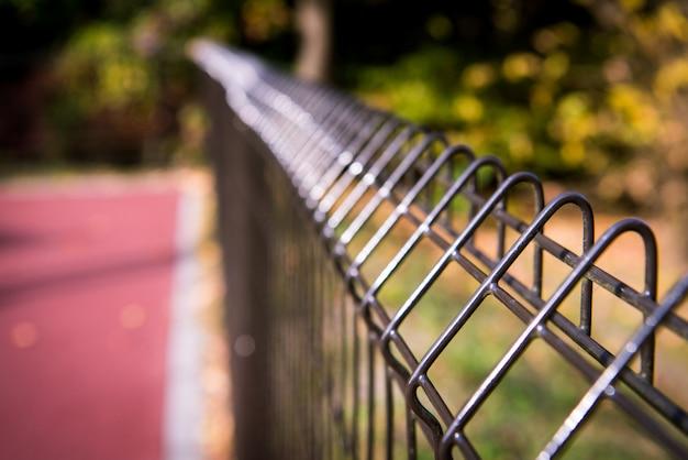 Recinto stridente d'acciaio del campo di calcio, cavo del recinto del metallo con erba nei precedenti. Foto Premium