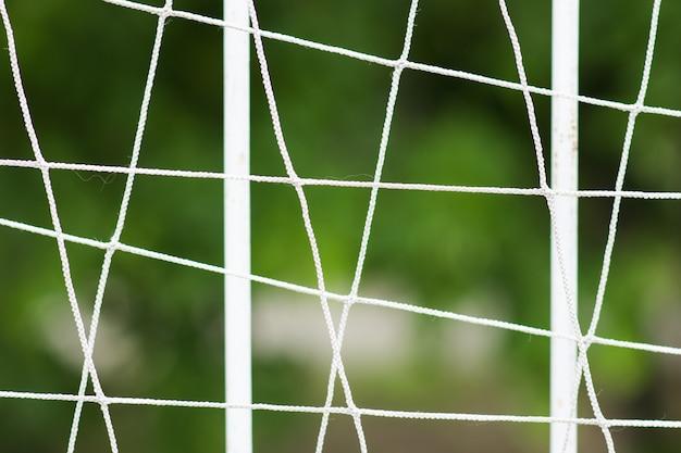 Recinto stridente d'acciaio del campo di calcio, recinto del metallo con il fondo della sfuocatura. Foto Premium
