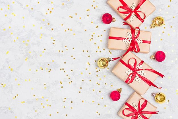 Regali di decorazioni di natale, glitter, palle, caramelle, fiocchi di neve su bac in calcestruzzo grigio Foto Premium