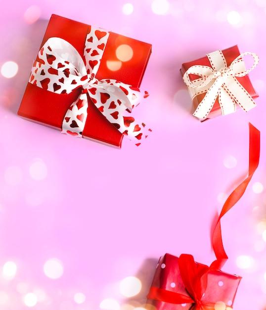 Regali di festa. scatole regalo rosso su rosa. san valentino . regalo di natale. Foto Premium