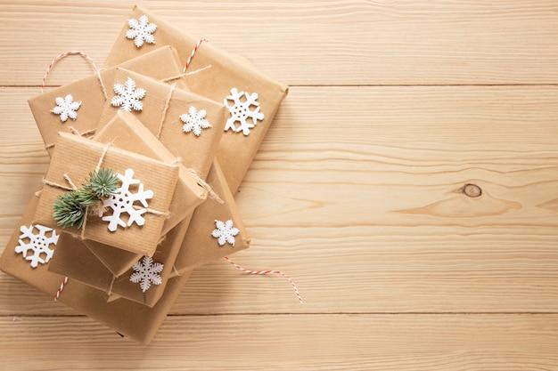 Regali festivi con fiocchi di neve su fondo di legno Foto Gratuite
