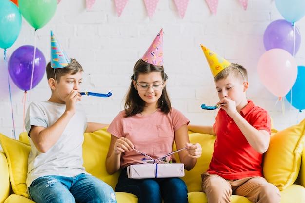 Regalo di compleanno scartare della ragazza mentre i suoi amici che saltano il corno del partito Foto Gratuite