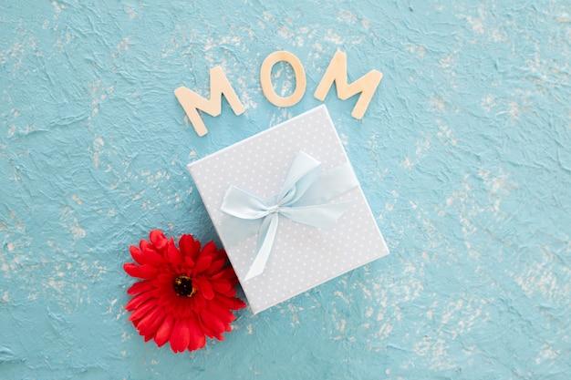 Regalo di giorno di madri con il fiore di redo su fondo leggero blu Foto Gratuite