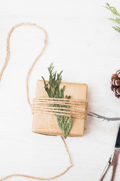 Regalo di natale avvolto con un ramoscello di abete Foto Gratuite