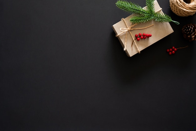 Regalo di natale su priorità bassa nera con i rami, le bacche e la corda del pino Foto Premium