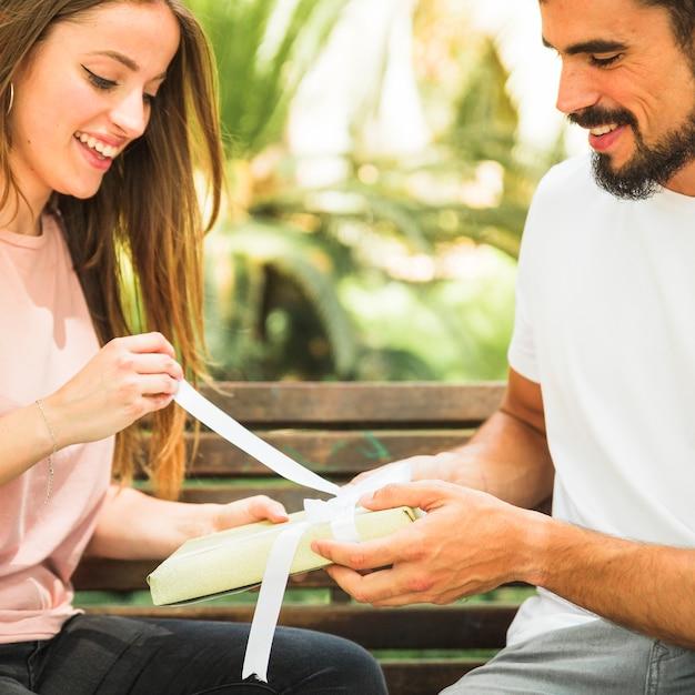 Regalo unwrapping sorridente della giovane donna comprato dal suo ragazzo Foto Gratuite