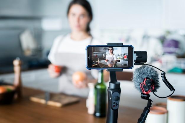 Registrazione femminile del vlogger che cucina radiodiffusione relativa a casa Foto Premium
