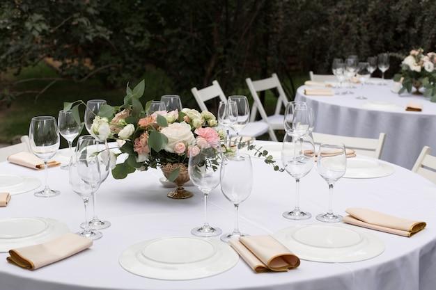 Regolazione della tabella di cerimonia nuziale decorata con i fiori freschi in un vaso d'ottone. tavolo per banchetti all'aperto per gli ospiti con vista sul verde Foto Premium