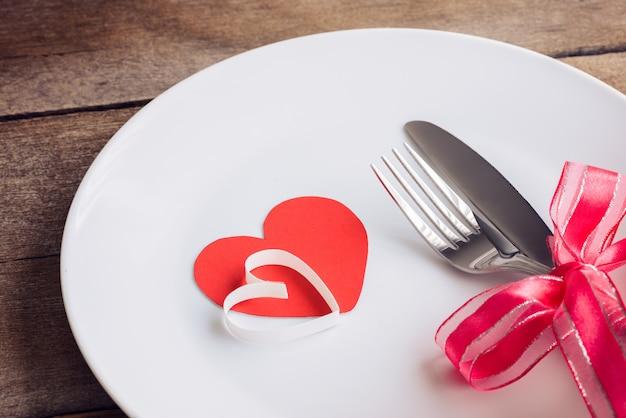 Regolazione della tavola di giorno di biglietti di s. valentino con il piatto, coltello, forcella, nastro rosso e cuori sulla tavola di legno Foto Premium