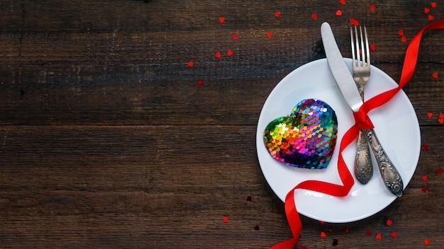 Regolazione festiva della tavola di san valentino con il cuore dell'arcobaleno sul piatto bianco e sui nastri rossi Foto Premium