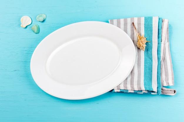 Regolazione marina della tavola con le coperture bianche delle decorazioni del mare e del piatto sul blu di legno Foto Premium