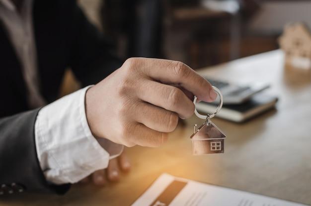 Responsabile del broker immobiliare che fornisce la chiave della casa al cliente dopo il contratto di firma Foto Premium