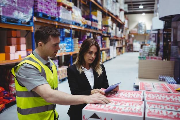 Responsabile e lavoratore del magazzino che esaminano compressa in magazzino Foto Premium