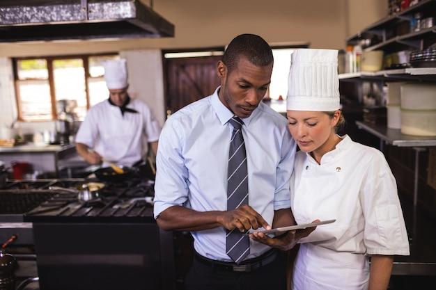 Responsabile maschio e cuoco unico femminile che utilizza compressa digitale nella cucina Foto Premium